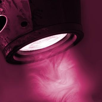 A light spotlight, shining through light smoke, colourised in purple