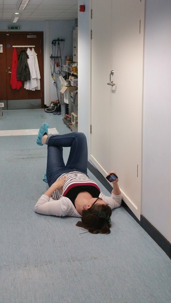 Hazel Lowe lying on the lab floor while waiting for the vacuum chamber to pumpdown during an experiment