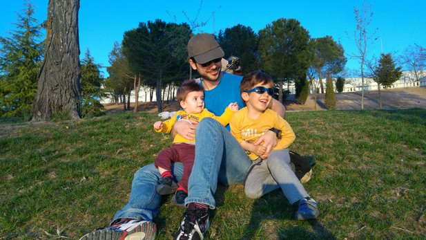 Modesto Redrejo-Rodriguez sitting on the grass, holding his sons