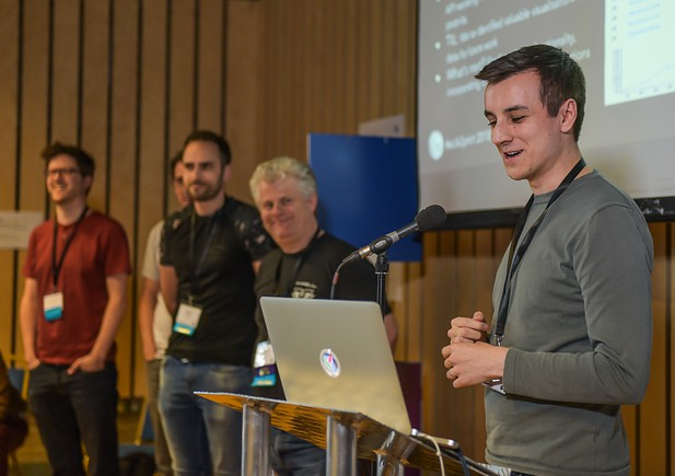The development team stand at a microphone for a presentation