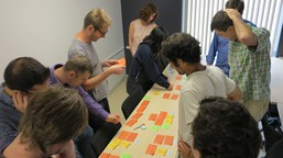 A group gather round a table covered in post-its at a collaborative design session for Texture