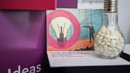 eLife postcard propped up again point of sale display saying Ideas, with lightbulb-shaped jar in foreground