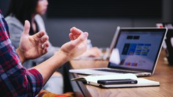 Hands gesturing in front of a laptop with woman in the backgroun