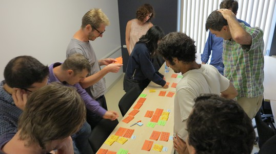 A group gather round a table covered in post-its