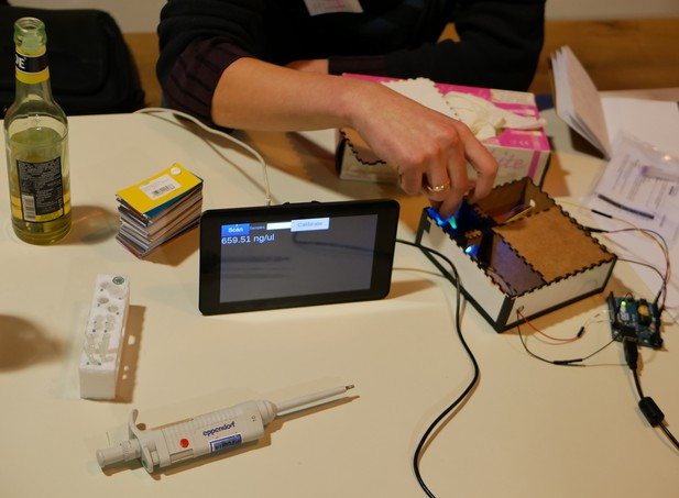 A person uses a custom-made fluorometer with the result displayed on a tablet
