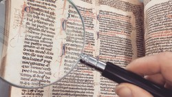 Magnifying glass held over ancient manuscript