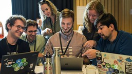 A team gather around a laptop